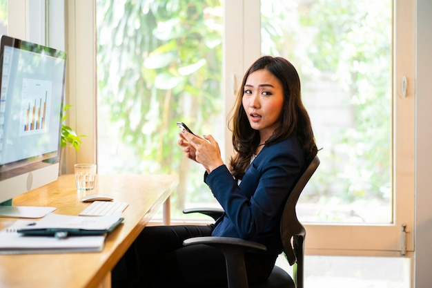 Business woman using mobile phone checking work assignment from office during her working from home.