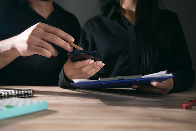 Business woman using mobile phone at office meeting