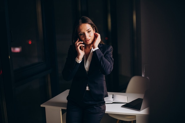 사무실에서 전화를 사용하고 밤 늦게 숙박하는 비즈니스 우먼
