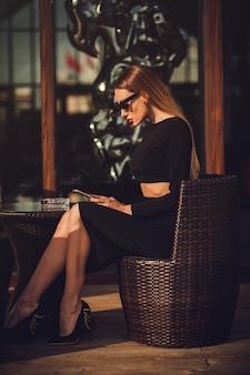 Business woman using phone on lunch break in terrace.