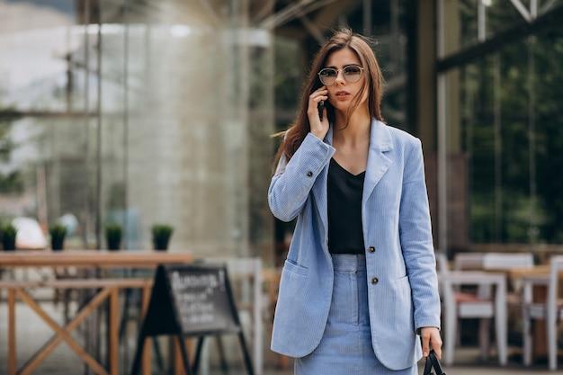 Деловая женщина по телефону за пределами улицы