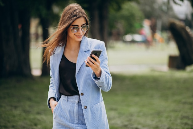 Business woman using phone in park
