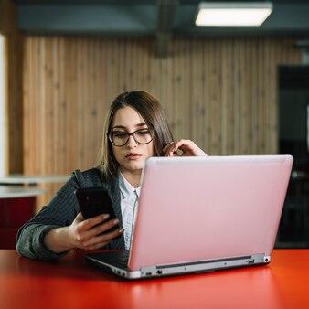 ビジネスの女性がノートパソコンのテーブルでスマートフォンを使用して