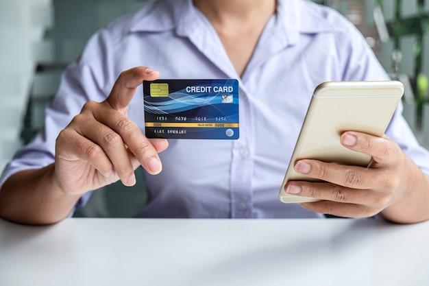 스마트폰, 노트북을 사용하고 신용 카드를 들고 세부 정보 페이지를 지불하는 비즈니스 여성은 카드 정보를 입력하기 위해 온라인 쇼핑 구매 및 입력 보안 코드를 표시합니다.