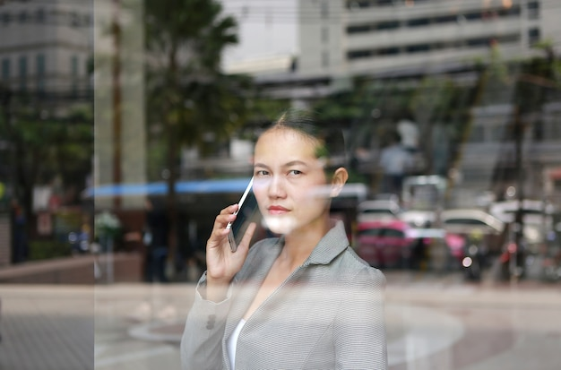 Business woman using a smartphone at reflection glass of office building.