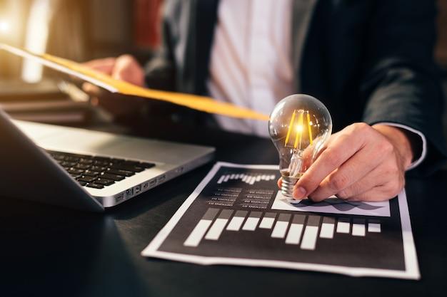 Деловая женщина, использующая смартфон, планшет и лампочку, с идеей, инновациями и творчеством. экономия денег с ручным размещением