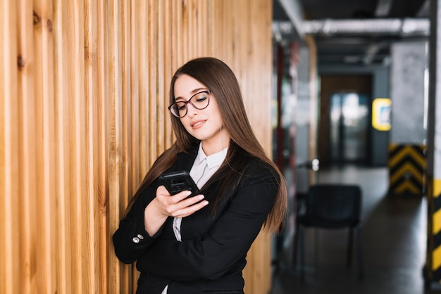 Business woman using smartphone at wooden wall