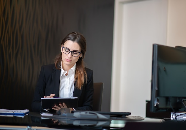 Business woman using a tablet in her company office, businesswoman career concept
