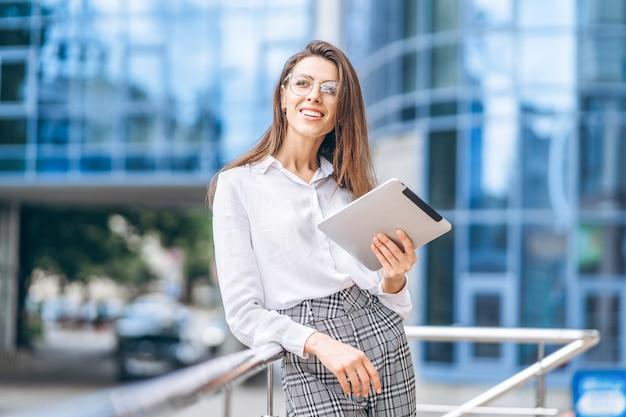 Business woman using tablet near modern business center.
