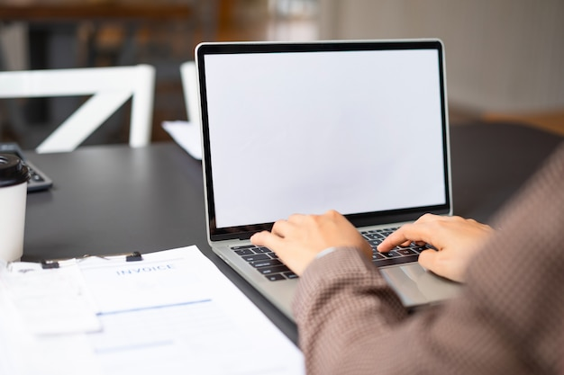 Business woman using and typing on mockup white screen laptop at her office.