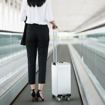 Business woman walking in airport terminal with trolley bag.