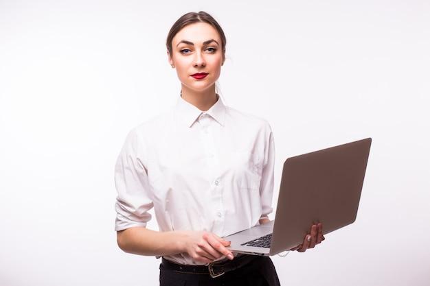 Donna di affari che cammina e che trasporta un computer portatile - sopra bianco