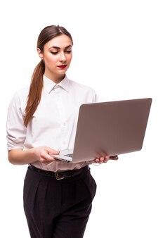 Donna di affari che cammina e che trasporta un computer portatile