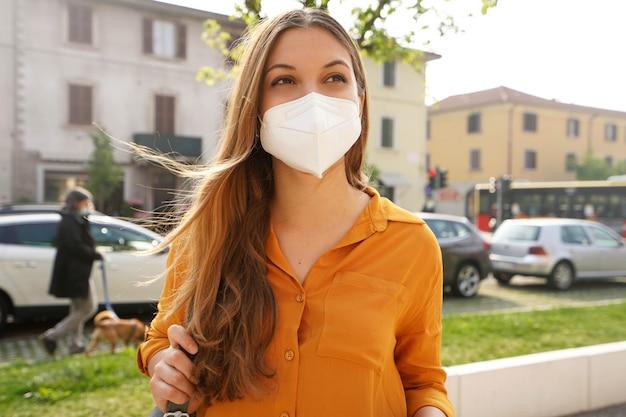 Kn95ffp2保護フェイスマスクを身に着けている街の通りを歩くビジネスウーマン
