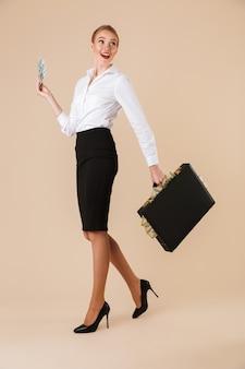Деловая женщина, идущая изолированным чемоданом с деньгами.