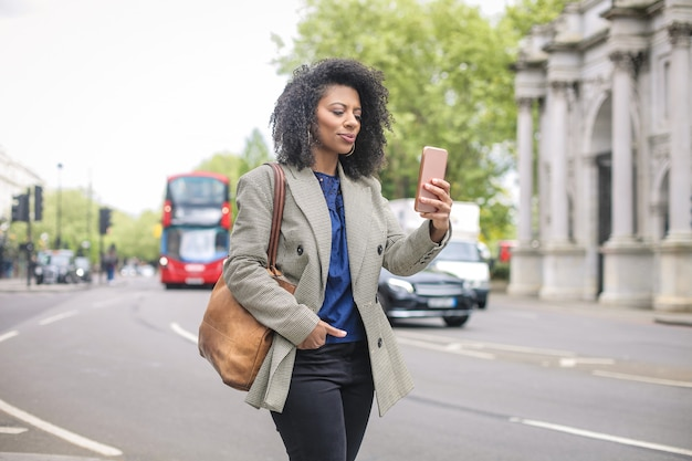Business woman walking in the street, checking her smart phone