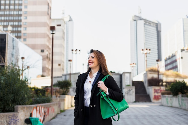 Business woman walking in street with bag