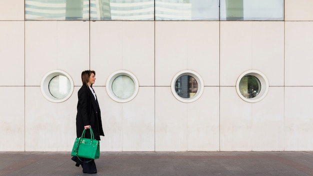 Business woman walking in street with green bag