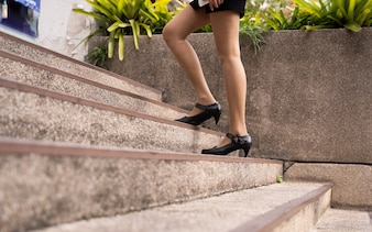 Business woman walking upstairs outdoors.