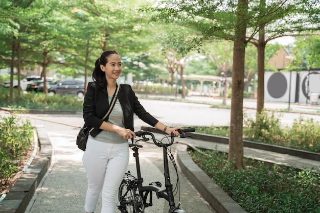 ビジネスの女性は電話を受けながら折りたたみ自転車の上を歩く