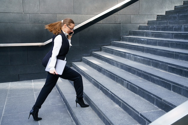 A business woman walks up the steps holding a tablet in her hand and talking on the phone.