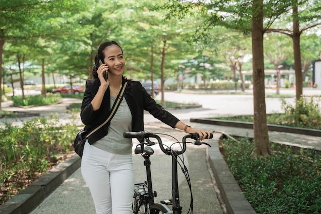 ビジネスの女性は電話を受けながら折りたたみ自転車で歩く