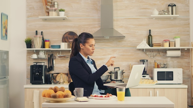 Business woman waving on video call during breakfast. young freelancer in the kitchen having a healthy meal while talking on a video call with her colleagues from the office, using modern technology a