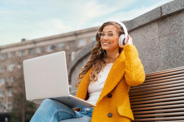 비즈니스 우먼 착용 안경 음악 헤드폰 야외 앉아 노트북을 사용하여 야외 옷을 입고 세련된 노란색 코트 미소 백인 여성 30대 밖에서 팟캐스트 또는 오디오 북 즐기기