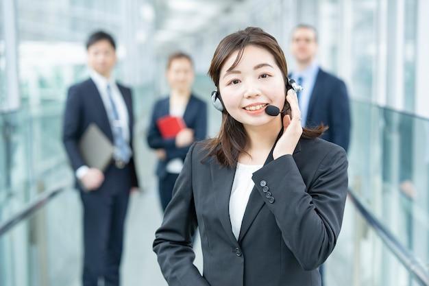 ヘッドセットを身に着けているビジネスウーマンと彼女のビジネスチーム