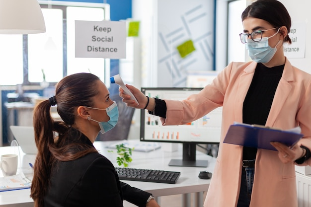 Business woman wearing face mask taking body temperature of colleague in company office using digital thermometer with infrared, during global pandemic with coronavirus, keeping social distancing.