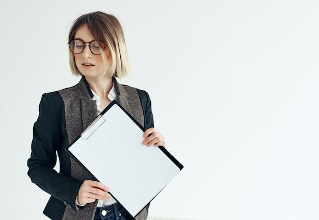 眼鏡をかけているビジネス女性は、オフィスの専門家の明るい背景を文書化します