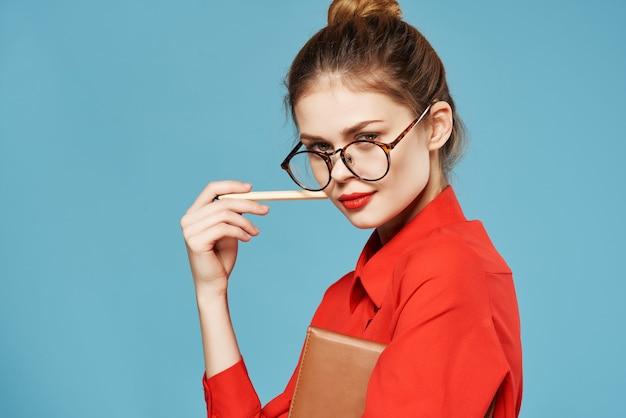 鉛筆の青い背景とメガネの赤いシャツのメモ帳を身に着けているビジネス女性