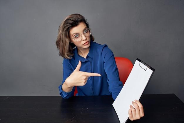 眼鏡をかけているビジネス女性は、テーブルの空白のシートのコピースペースに座っています