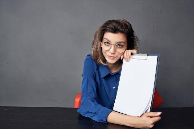眼鏡をかけているビジネスの女性は、テーブルの空白のシートのコピースペースに座っています