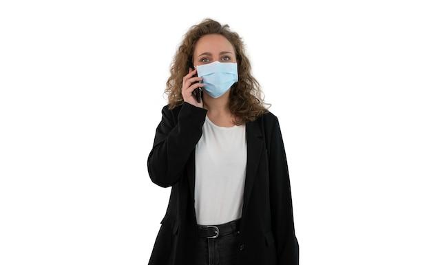 Деловая женщина в маске для предотвращения covid разговаривает по телефону изолированно