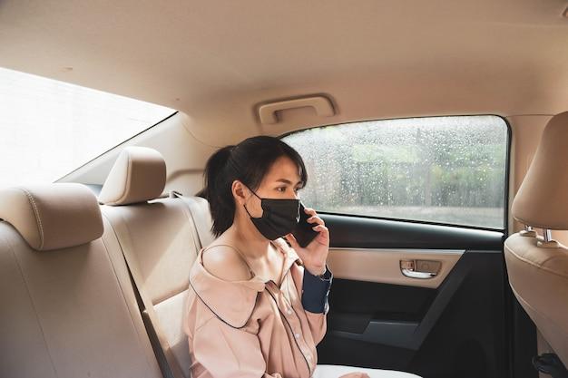 Деловая женщина в защитной маске разговаривает по мобильному телефону, сидя на заднем сиденье в машине