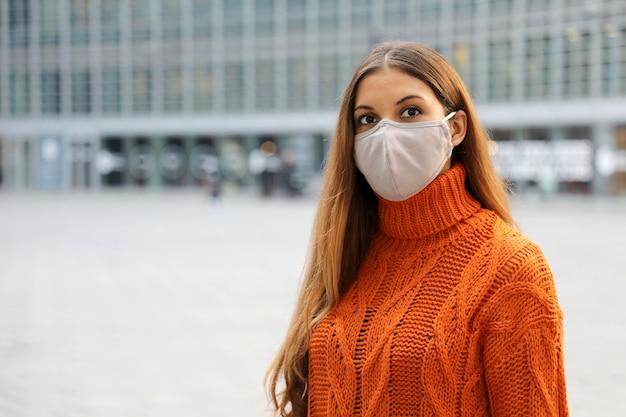 通りに立っている保護マスクを身に着けているビジネスウーマン