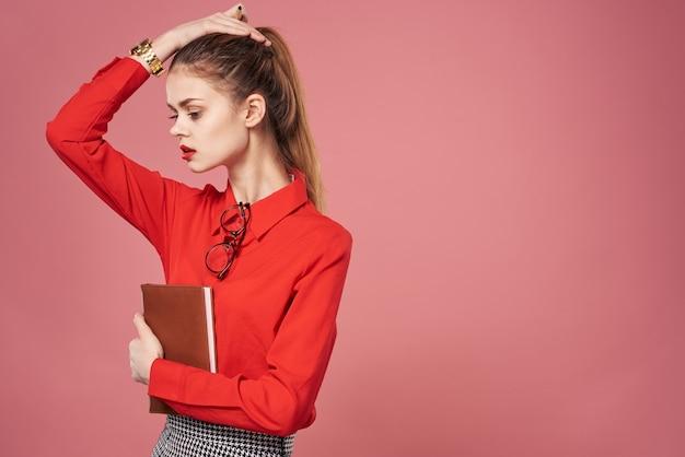 Notebloc를 들고 빨간 셔츠를 입고 비즈니스 우먼