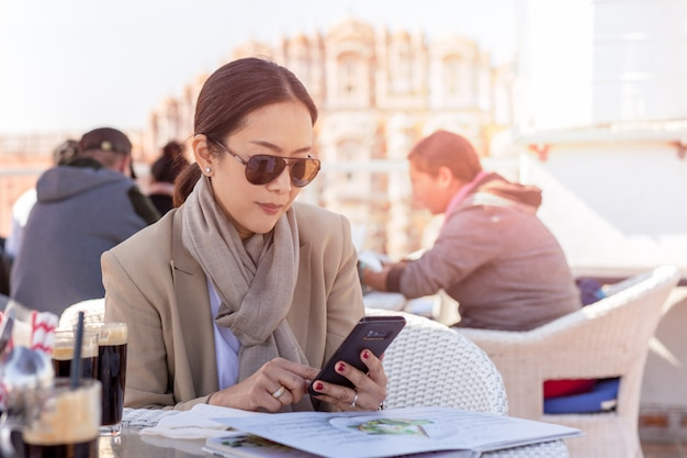 Business woman wearing sunglasses looking at cell phone in hands