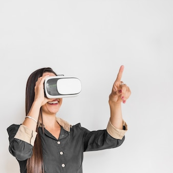 Business woman wearing vr glasses and pointing out