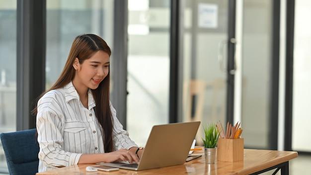 近代的なオフィスでラップトップでタイプしている間ビジネスの女性。
