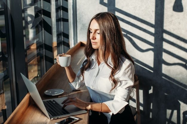 Business woman in white blouse using laptop, drinks coffee at table in cafe
