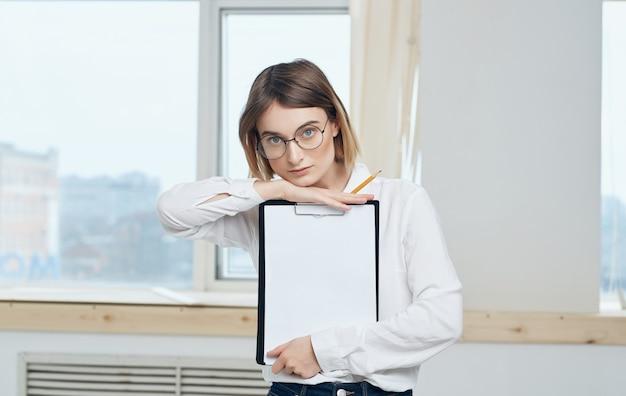 ビジネスウーマンの白いシャツは、窓の近くのオフィスを文書化します