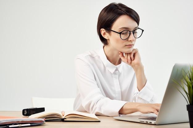 Деловая женщина в белой рубашке перед работающим секретарем ноутбука