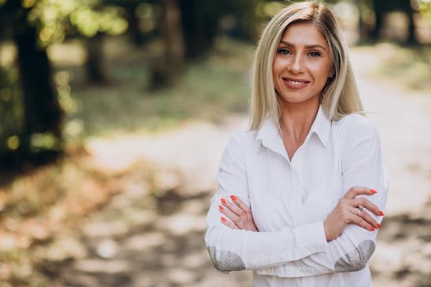 Donna d'affari in camicia bianca nel parco