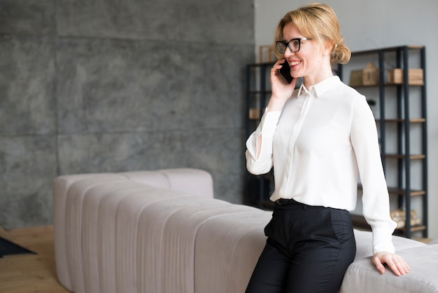 Business woman in white shirt talking on phone