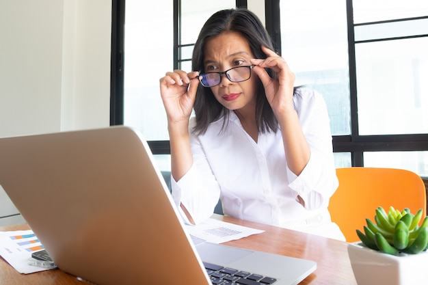 Business woman in white shirt wear glasses sitting on workplace