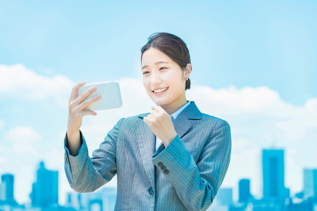 A business woman who enthusiastically looks at the screen of a smartphone