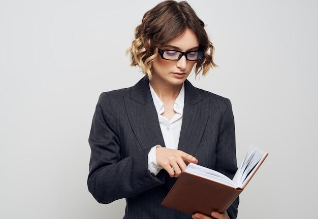 明るい背景の古典的なスーツのファッショナブルな髪型で彼女の手に本を持つビジネス女性