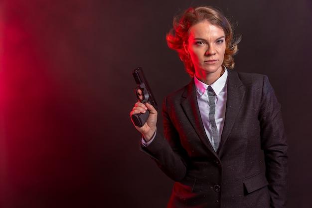 Деловая женщина с пистолетом в руке. портрет на черном фоне. копировать пространство